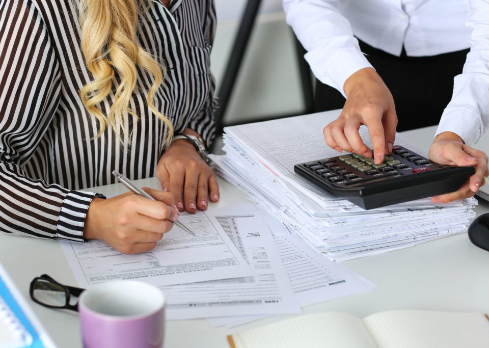 47600599 - two female accountants counting on calculator income for tax form completion hands closeup. internal revenue service inspector checking financial document. planning budget, audit concept